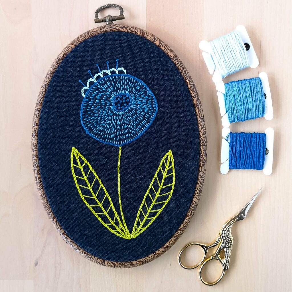 Blue modern flower on navy blue fabric hand embroidery in oval frame