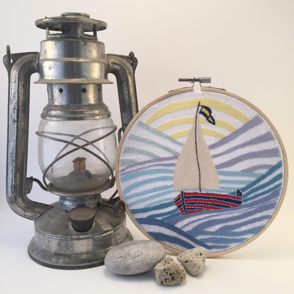 Sailboat hand embroidery in a hoop with lamp and stones