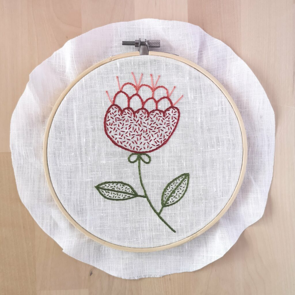 Red flower embroidery in a hoop, framing process