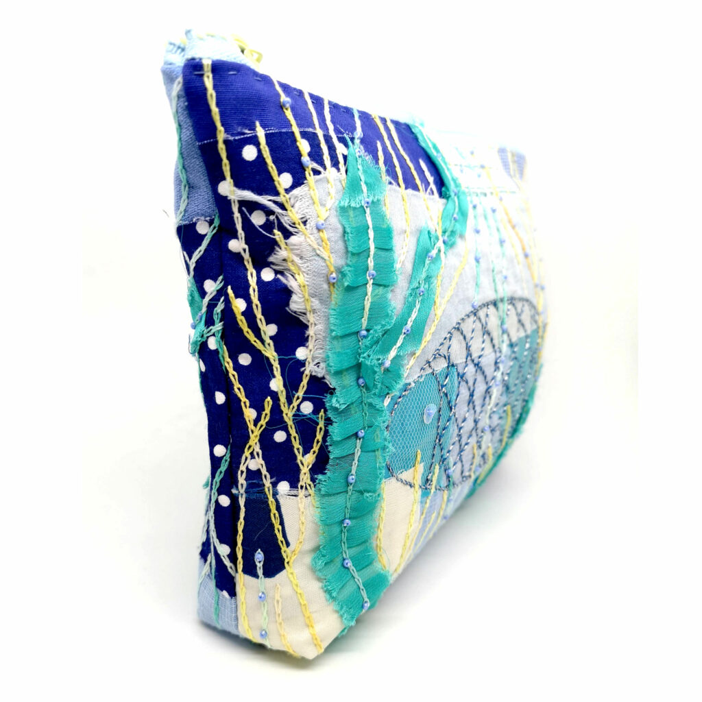 Blue cosmetic bag embroidered with a fish
