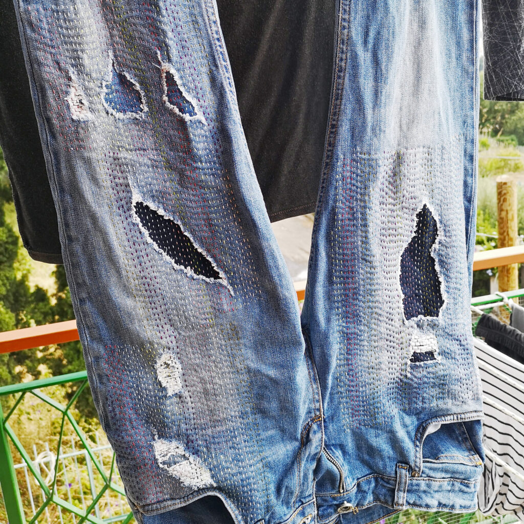 Hand embroidered jeans hanging to dry