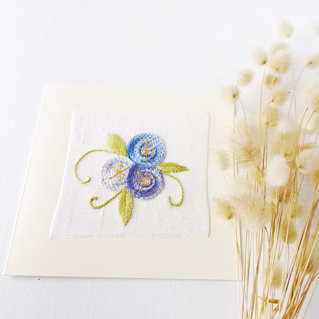 Hand embroidered postcard with blue flowers in chain stitch